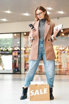 Stylowa młoda kobieta podczas zakupów w centrum handlowym znajduje zniżki w sklepach z aplikacją na smartfony