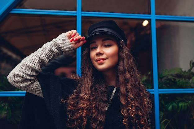 Stylowa młoda kobieta pozowanie przed niebieskim oknie na zewnątrz. modny strój. piękny model z uśmiechniętymi kręconymi włosami