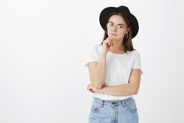 Stylowa młoda kobieta pozuje na białej ścianie