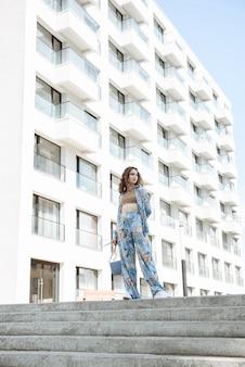 Stylowa młoda kobieta pozuje w nowej kolekcji ubrań w katalogu miejskim