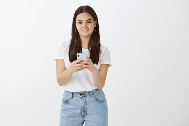 Stylowa młoda kobieta pozuje z jej telefonem na białej ścianie