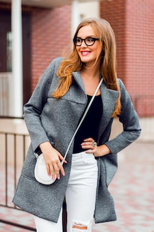 Stylowa młoda kobieta spacerująca po ulicy w ładny słoneczny jesienny dzień, ubrana w płaszcz vintage i okulary przeciwsłoneczne.