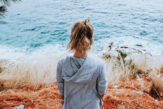 Stylowa młoda kobieta stojąca przy niezwykłym brzegu w letni dzień i odwracając wzrok. koncepcja podróży i wakacji.