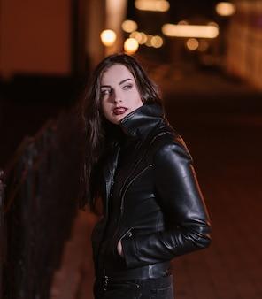 Stylowa młoda kobieta stojąca w mieście w nocy.