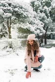 Stylowa młoda kobieta ubrana w ciepłe ubrania, dotykając śniegu i ciesząc się weekendem w zimie