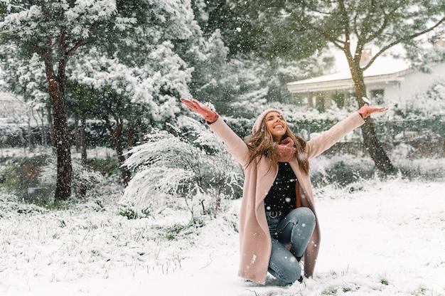 Stylowa młoda kobieta ubrana w ciepłe ubrania, rzucając śnieg i ciesząc się weekendem w zimie