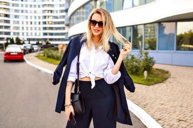 Stylowa młoda kobieta ubrana w modny granatowy garnitur, pozuje w pobliżu nowoczesnych budynków, modne dodatki, uśmiechnięty koniec ciesząc się wolnym słonecznym letnim dniem, spacerując w pobliżu biura.