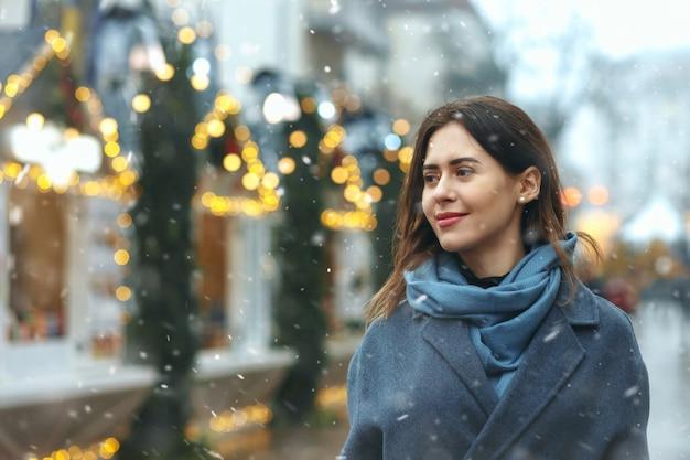 Stylowa młoda kobieta ubrana w modny płaszcz spaceru na ulicy podczas opadów śniegu. pusta przestrzeń
