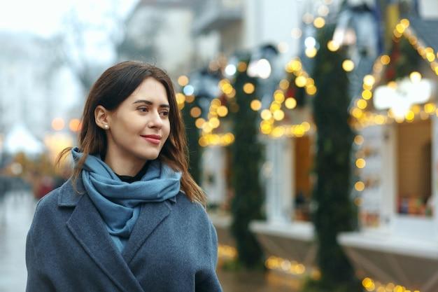 Stylowa młoda kobieta ubrana w modny płaszcz spaceru na ulicy w zimie. pusta przestrzeń