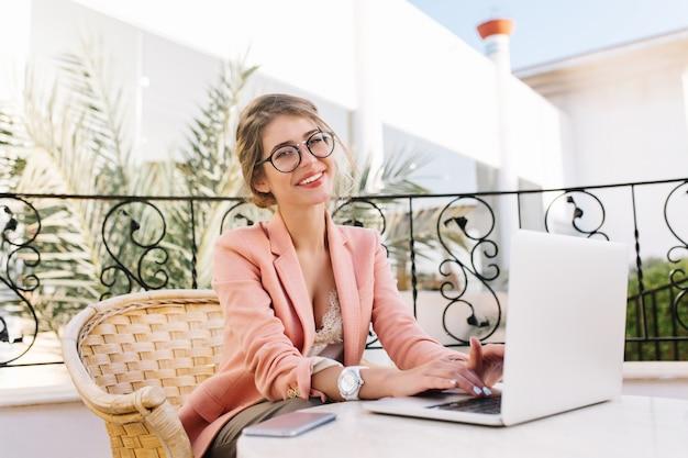 Stylowa młoda kobieta uśmiecha się i pracuje na laptopie, radosna dziewczyna wpisując na klawiaturach, siedząc w wiklinowym krześle w przytulnej kawiarni na świeżym powietrzu. nosi stylowe okulary, różową marynarkę, beżową bluzkę, białe zegarki.