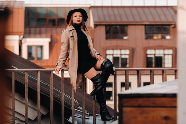 Stylowa młoda kobieta w beżowym płaszczu i czarnym kapeluszu siedzi na dachu w centrum miasta. moda uliczna dla kobiet. jesienna odzież. miejski styl.