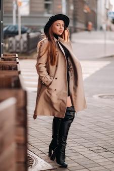 Stylowa młoda kobieta w beżowym płaszczu w czarnym kapeluszu na ulicy miasta. moda uliczna dla kobiet. jesienna odzież. miejski styl.