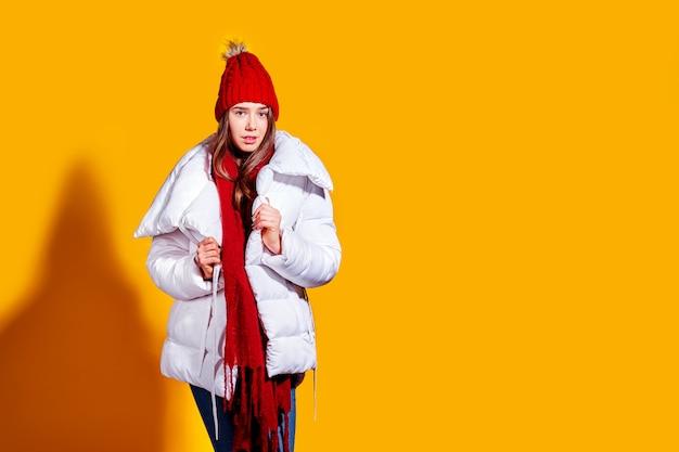 Stylowa młoda kobieta w białym płaszczu i dzianinowym czerwonym kapeluszu