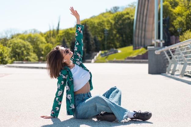 Stylowa młoda kobieta w dorywczo zielonej koszuli w słoneczny dzień, pozowanie, siedzi na mostku w uszach bezprzewodowych słuchawek bluetooth