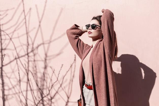 Stylowa młoda kobieta w modnych okularach przeciwsłonecznych w modnym płaszczu stoi i cieszy się ciepłym słońcem w pobliżu różowego budynku. śliczna dziewczyna modelka odpoczywa w pobliżu ściany na ulicy w słoneczny dzień wiosny.