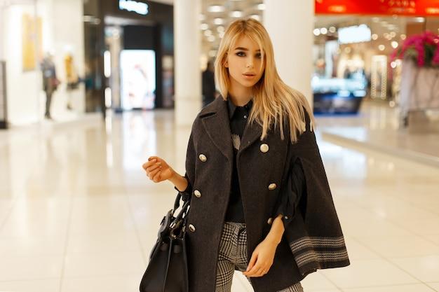 Stylowa młoda kobieta w modnym szarym płaszczu ze stylową torbą na zakupy w centrum handlowym