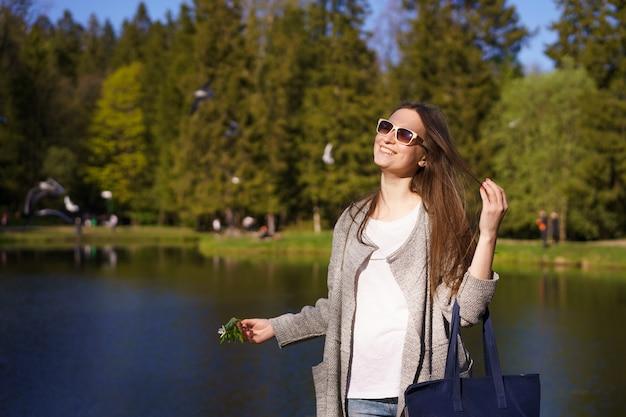 Stylowa młoda kobieta w okularach przeciwsłonecznych z torbą i kwiatkiem w dłoniach spaceruje na tle jeziora w słoneczny dzień