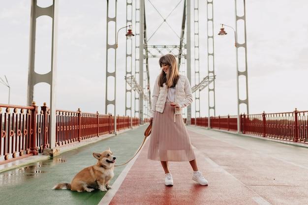 Stylowa młoda kobieta w pełnym wymiarze bawi się z psem w mieście
