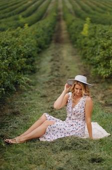 Stylowa młoda kobieta w różowej niebieskiej sukience vintage i kapeluszu pozowanie w zielonym polu
