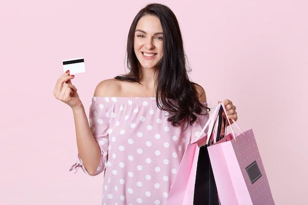 Stylowa młoda kobieta w sukience w groszki, trzymająca torby na zakupy i kartę kredytową, stoi uśmiechnięta na różowo, ma przyjemny wyraz twarzy, wyraża radość i radość.