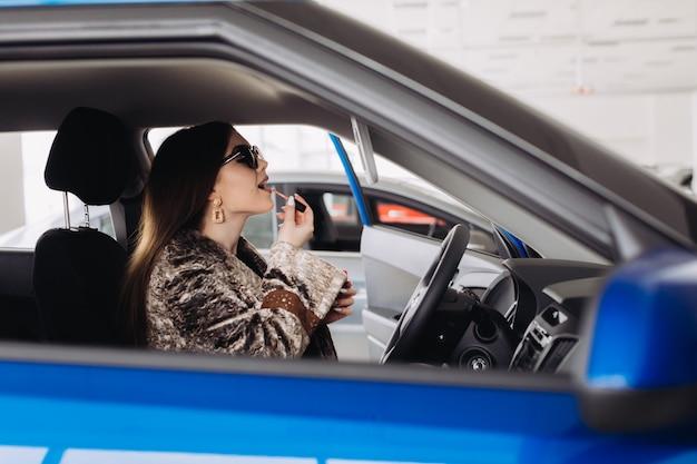 Stylowa młoda kobieta wybiera nowy samochód w sklepie samochodowym