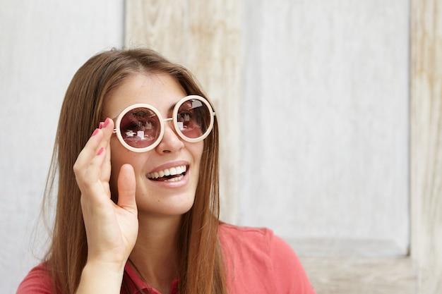 Stylowa młoda kobieta z różowymi paznokciami, dopasowując okrągłe okulary przeciwsłoneczne, relaksując się w pomieszczeniu w słoneczny dzień. ładna studentka z szczęśliwym uśmiechem spędza poranek w domu przed pójściem na studia