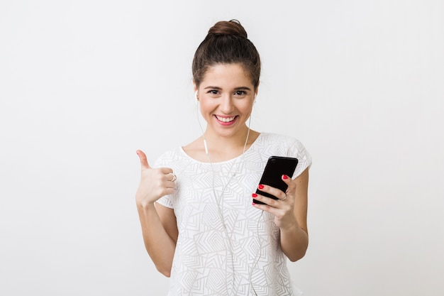 Stylowa młoda ładna kobieta uśmiechnięta w koszulce, słuchanie muzyki w słuchawkach, trzymanie smartfona, używanie urządzenia, odizolowany, pokazujący kciuk w górę, szczęśliwy, pozytywny gest
