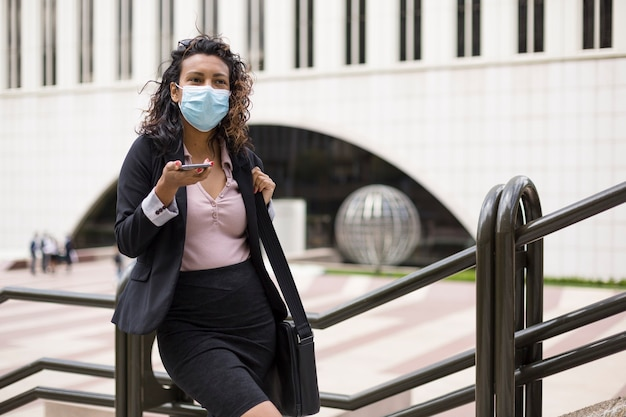 Stylowa młoda latynoska kobieta z maską na twarz. osoba przedsiębiorcza w dniu pracy podczas covid-19.