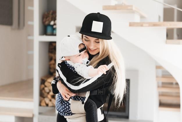 Stylowa młoda mama trzyma w domu plecak ergo swojego uroczego rocznego dziecka w pięknym wnętrzu wygoda dla mamy.