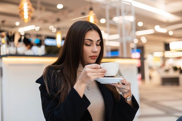 Stylowa młoda piękna brunetka kobieta z długimi włosami w czarnym modnym płaszczu z filiżanką kawy odpoczywa w kawiarni w centrum handlowym. śliczna atrakcyjna nowoczesna dziewczyna w modnych ubraniach cieszy się gorącym napojem w pomieszczeniu