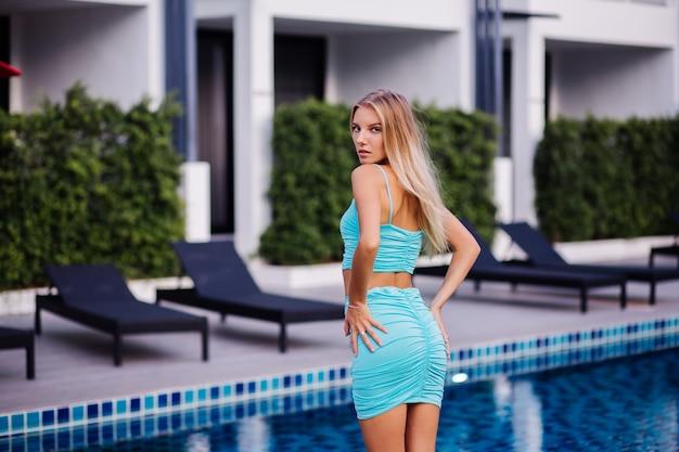 Stylowa młoda piękna szczupła blondynka w lato niebieski top i krótką spódniczkę