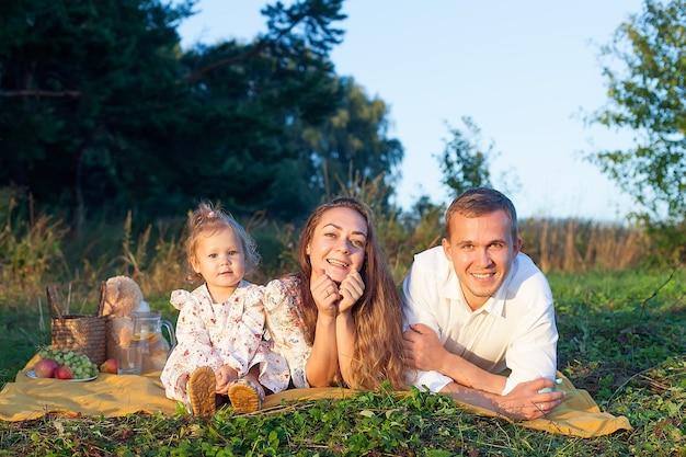 Stylowa młoda rodzina mamy, taty i córki roczna blondynka siedzi obok ojca na ramionach, na świeżym powietrzu za miastem w parku wśród drzew latem. noś dżinsy.