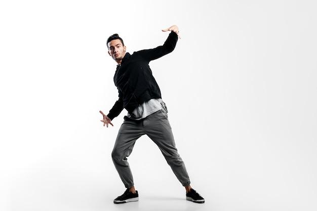 Stylowa młoda tancerka ubrana w czarną bluzę i szare spodnie tańczy hip-hop na białym tle