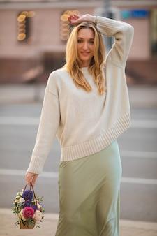 Stylowa młoda uśmiechnięta kobieta na sobie ubranie z chodzeniem bukiet kwiatów. uliczna moda damska. zdjęcie wysokiej jakości