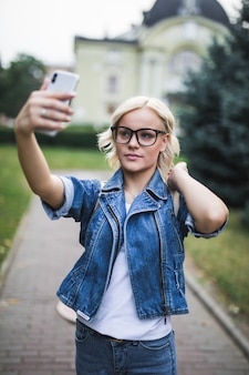 Stylowa moda blondynka kobieta w dżinsach suite sprawia, że selfie na swoim telefonie w mieście rano
