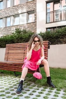 Stylowa modelka w różowej sukience pozuje siedząc na ławce na świeżym powietrzu w mieście