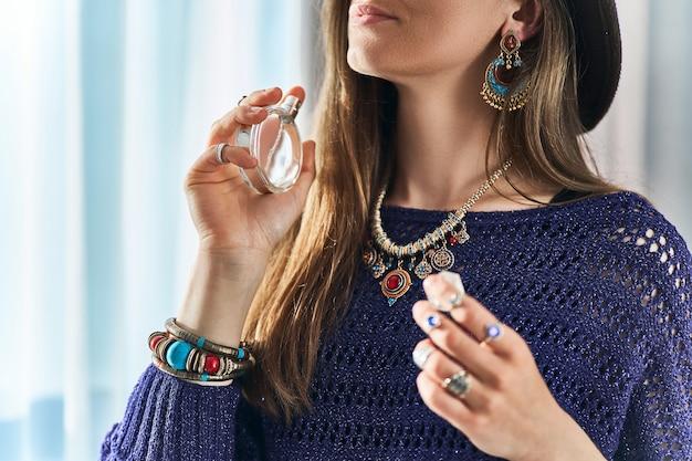 Stylowa modna brunetka boho chic kobieta nosząca biżuterię trzyma butelkę perfum