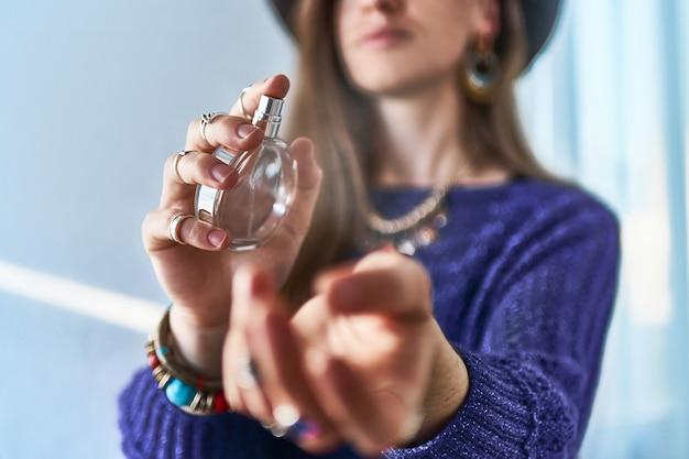 Stylowa modna brunetki kobieta w kapeluszu jest ubranym biżuterię stosuje perfumy na jej nadgarstku