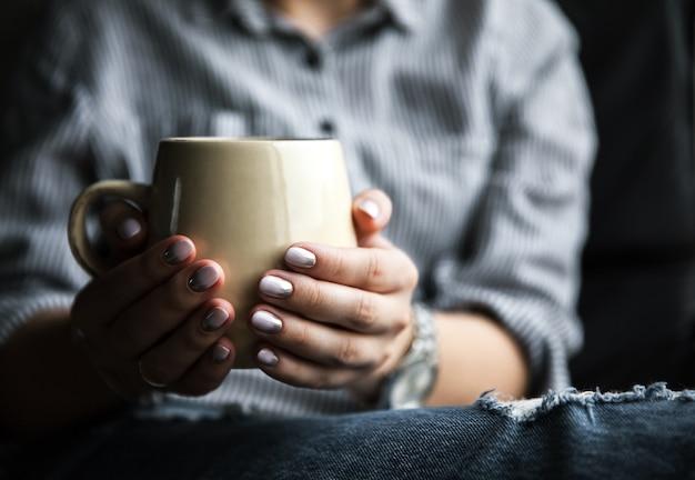 Stylowa modna dziewczyna z filiżanką kawy i manicure w dżinsach. moda, pielęgnacja, uroda