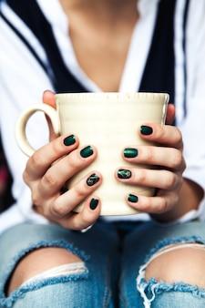 Stylowa modna dziewczyna z filiżanką kawy i zielonym manicure w dżinsach. moda, pielęgnacja, uroda