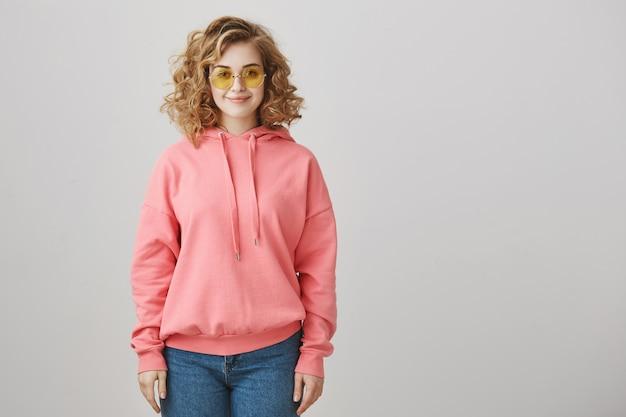 Stylowa modna dziewczyna z kręconymi włosami w okularach przeciwsłonecznych