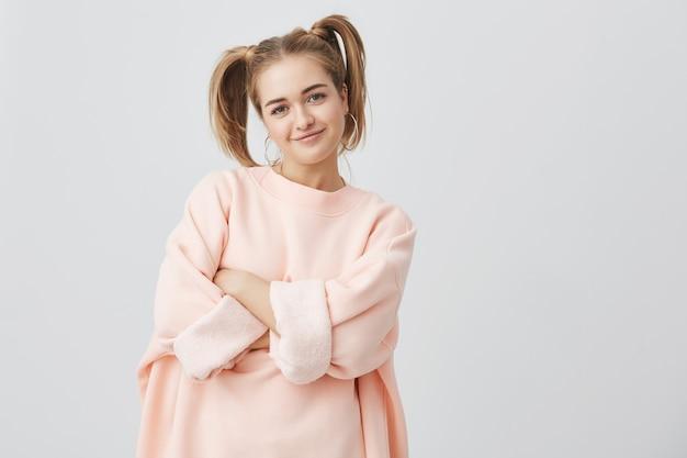 Stylowa, modna, ładna dziewczyna w różowej bluzie z długimi rękawami z dwoma kucykami i dużym okrągłym uchem, stwarzającym, z założonymi rękami. dziewczyna uśmiecha się, wyrażając pozytywne emocje.