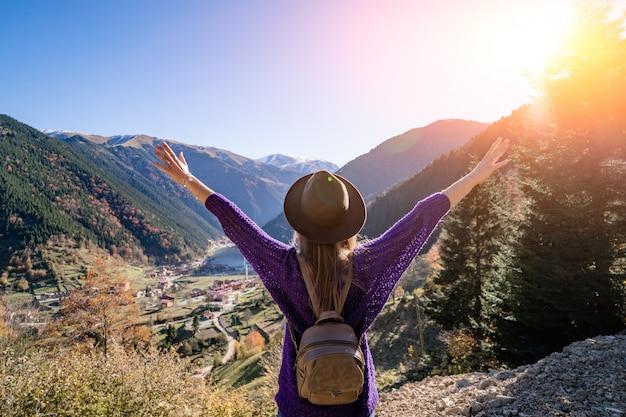 Stylowa, modna podróżniczka wolna hipster w brązowym kapeluszu z plecakiem stoi z wyciągniętymi ramionami w górach i jeziorem uzungol w trabzon podczas podróży po turcji