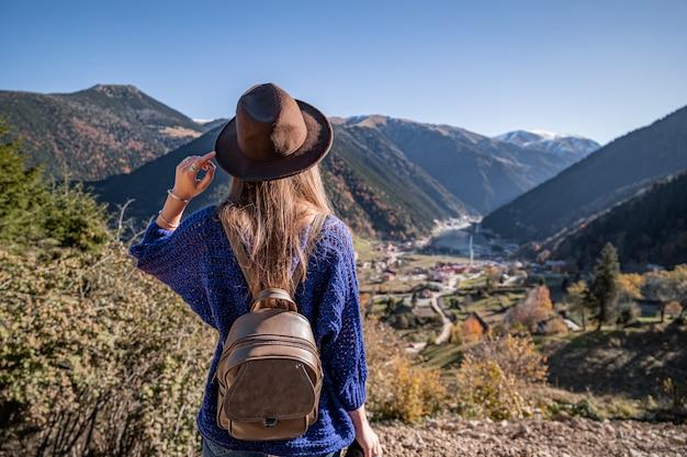 Stylowa modna podróżniczka z darmową hipsterką w brązowym kapeluszu z plecakiem w górach i jeziorem uzungol w trabzon podczas podróży po turcji