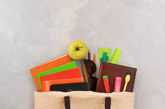 Stylowa modna torba wiklinowa z podręcznikami i zeszytami, zielonym jabłkiem i długopisami w postaci ananasa, arbuza, kaktusa, innych artykułów piśmiennych i okularów przeciwsłonecznych.