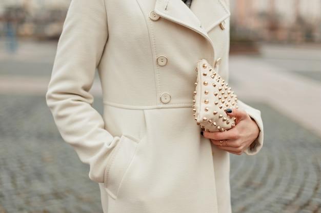 Stylowa modna torebka w dłoni modna kobieta w płaszczu trzyma torebkę
