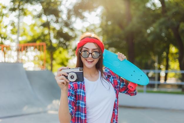 Stylowa modniś kobieta trzyma deskorolka i retro kamerę w rękach w jaskrawym słonecznym dniu. koncepcja młodzieży