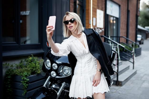Stylowa motocyklistka w modnych ubraniach (biała sukienka, czarne skórzane kurtki, okulary przeciwsłoneczne)
