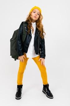 Stylowa nastolatka w białej koszuli, skórzanej czarnej kurtce, żółtych spodniach i żółtym kapeluszu, z plecakiem na ramionach pozującym na białym