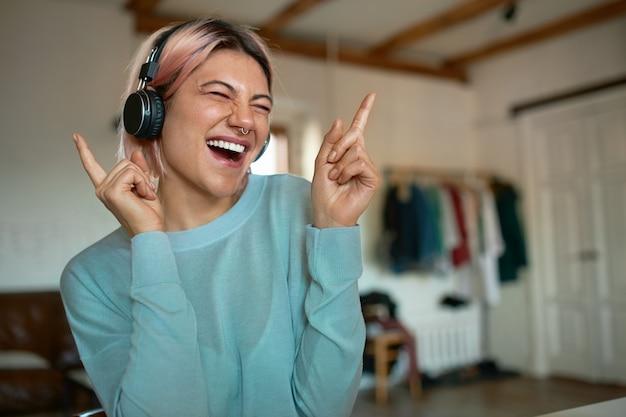 Stylowa nastolatka z różowymi włosami i kolczykiem na twarzy bawi się w domu, będąc sama w domu, słuchając muzyki w słuchawkach bezprzewodowych, zamykając oczy, wykonując ruchy taneczne, śpiewając razem z